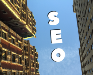 SEO search engin optimization written as clouds in a sky between two tall buildings as viewed from the ground.